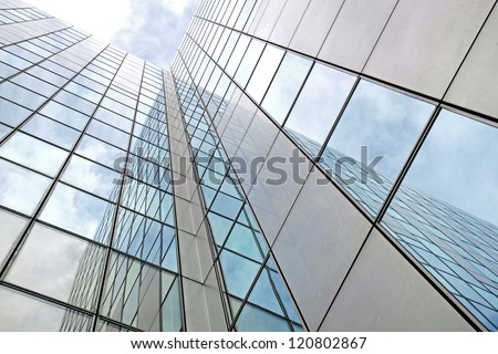 modern facade of glass and steel reflecting clouds - stock photo