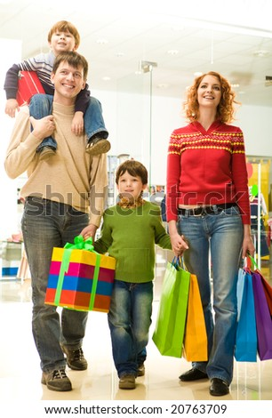 Modern family going shopping in trade center before Christmas time - stock photo