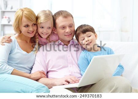 Modern family networking with laptop at home - stock photo