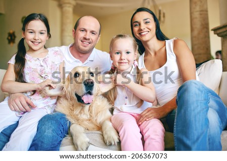 Modern family of father, mother, two daughters and dog posing for camera at home - stock photo