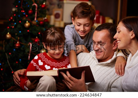Modern family of four reading Christmas fairy tales - stock photo