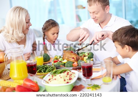 Modern family sitting at festive table and going to eat roasted turkey, young man cutting it - stock photo