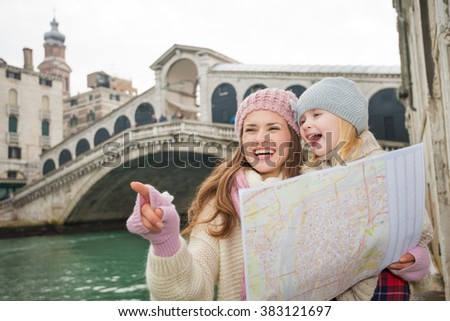 Modern family taking a winter break to enjoy inspirational adventure in Venice, Italy. Mother with map pointing daughter on something while standing in front of Ponte di Rialto - stock photo