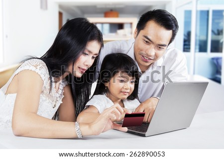 Modern family using a laptop computer and credit card to online shopping at home - stock photo