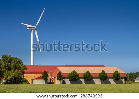 Modern Farm barns with wind turbine as an example of the new agricultural economy - stock photo