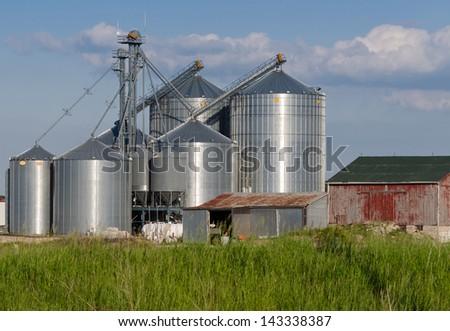 Modern farm silo and an old barn - stock photo