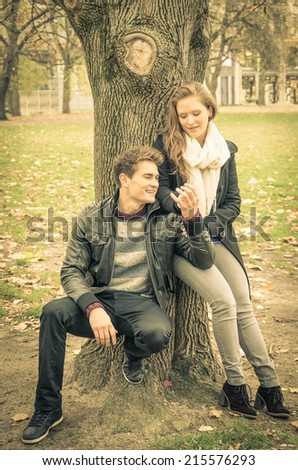 Modern fashion hipster couple of young lovers with autumn clothes - Deep moment at the beginning of a love story with a nostalgic desaturated filtered look - stock photo