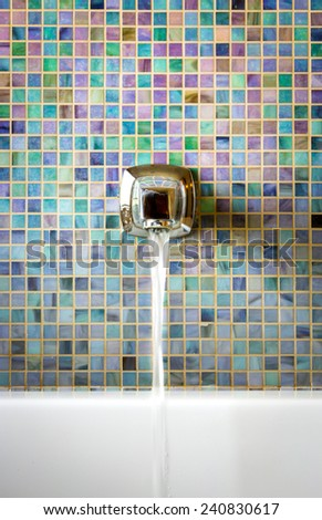 Modern faucet against a mosaic glass tile wall with running water - stock photo