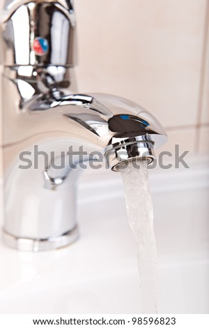 Modern Faucet closeup with streaming water flow - stock photo