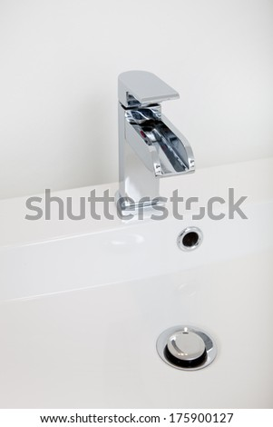 Modern faucet with a silver chrome finish metal tap fitting and a retractable plug in a modern white hand basin - stock photo