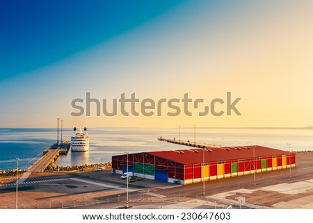 Modern Ferry At Pier Awaiting Loading Cargo From Port And Passenger Boarding And From Terminal. Early Morning With Beautiful Sunrise Sky, Summer Time. - stock photo