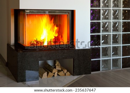modern fireplace in the apartment interior with real fire - stock photo