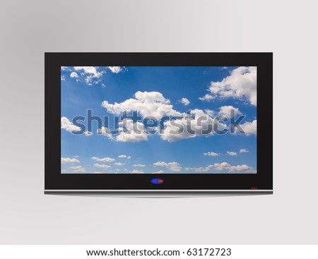 Modern flat television set with cloudscape on screen,  over a gray wall - stock photo