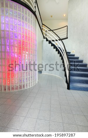 Modern foyer with glass block wall trim in multi color lights. View of staircase - stock photo