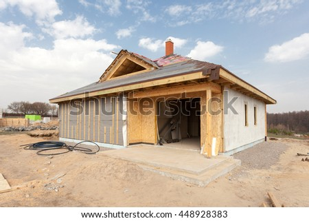 Modern frame energy efficient house under construction with membrane coverings, roof shingles and insulation materials - stock photo