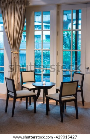 Modern furnished dining room, wooden table, chairs with glass window classic style. Simple writing table luxurious room and decorate in a classic white interior. Image have worm light in luxury room - stock photo