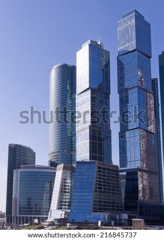 Modern, futuristic skyscrapers and city office buildings in Moscow (Russia) with reflections in glass wall windows with a blue sky and clouds as a background. - stock photo