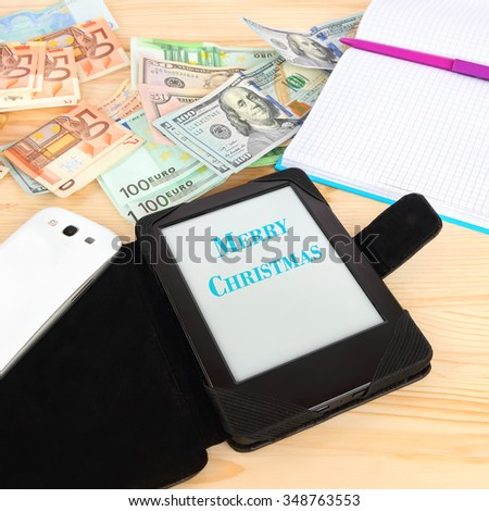 Modern gadgets tablet with Merry Christmas greeting, smart phone and classic notebook. Money (banknotes euro and USA dollars) in the background. Modern gadgets and retro office accessories with money - stock photo
