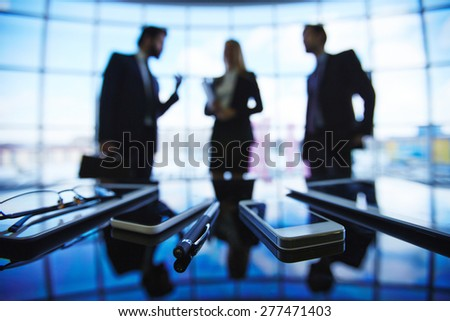 Modern gadgets with pen on background of business group talking - stock photo