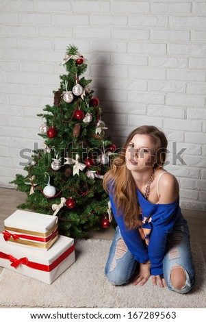 Modern girl near New Year's tree - stock photo