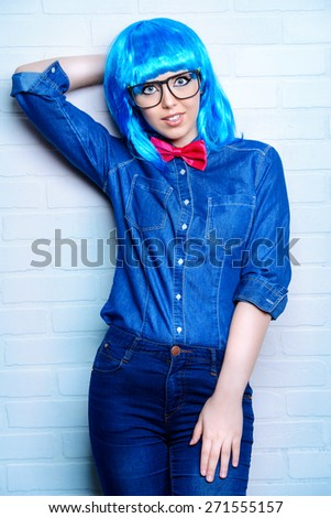 Modern girl wearing bright blue wig and jeans clothes posing by the urban white brick wall. Beauty, fashion. - stock photo