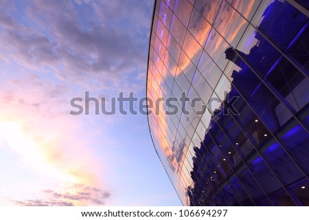 Modern glass building with reflected evening city and sunset sky in it - stock photo