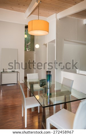 Modern glass dining table with white leather chairs and pendent with entry in modern home.  - stock photo