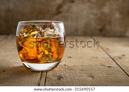 Modern glass of scotch whisky old vintage wooden barrel background lifestyle pub fine art craft bourbon - stock photo