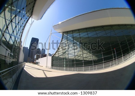 Modern glass, steel, and concrete architecture with downtown skyscrapers in the background. Feeling is kept bleek, cool, angular. Good as background. - stock photo