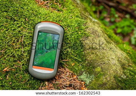 Modern GPS navigation on the floor of green forest - stock photo