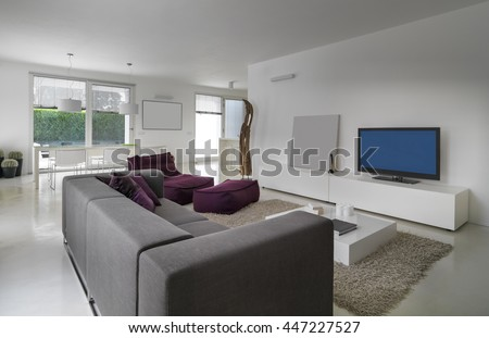 modern gray sofa and purple armchair in the modern living room - stock photo