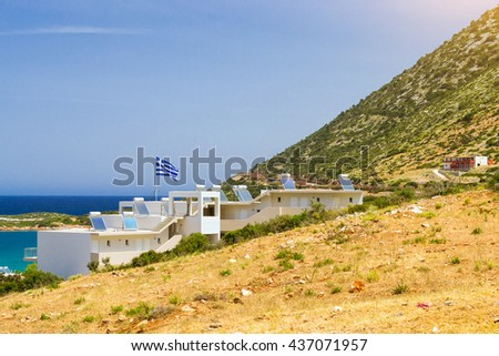 Modern Greek architecture, white building in constructivist style, stands on shore of Cretan sea, on roof mounted solar panels with water heaters, on flagpole the flag of Greece. Bali, Crete, Greece - stock photo