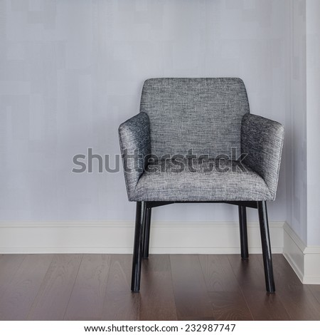 modern grey chair with blue wall and wood floor at home - stock photo
