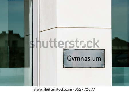 Modern gymnasium school sign on a marble wall next to the entrance of a study environment which provides advanced secondary education - stock photo