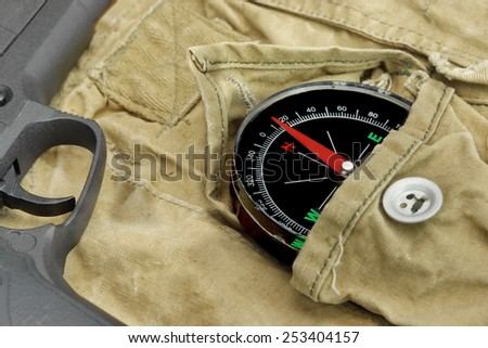 Modern Handgun and Compass On The Weathered Backpack - stock photo