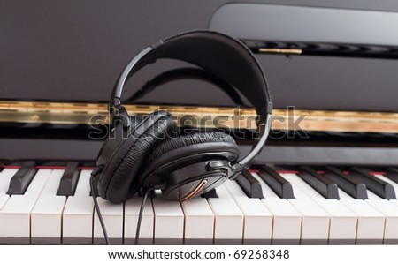 Modern headset on a classic black grand piano keyboard. - stock photo