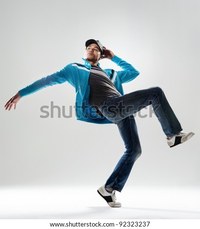 modern hip hop dancer lifts his leg and does some moves while dressed in trendy modern clothing - stock photo