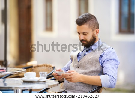 Modern hipster businessman drinking espresso coffee in the city cafe during lunch time and using mobile phone - stock photo