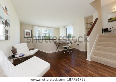 Modern home home office interior with furniture and wooden floor and stairway - stock photo