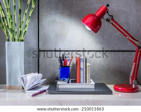 Modern home office desk with laptop, lamp and vase of flowers - stock photo