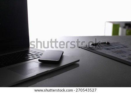 Modern home office with computer and laptop, folder, phone lying on the desk - stock photo