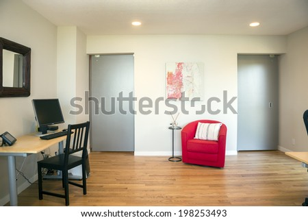 Modern home office with red armchair and grey sliding doors.  - stock photo