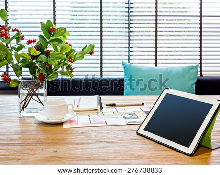 Modern home office workspace with tablet, architecture hand-drawn illustration on table - stock photo