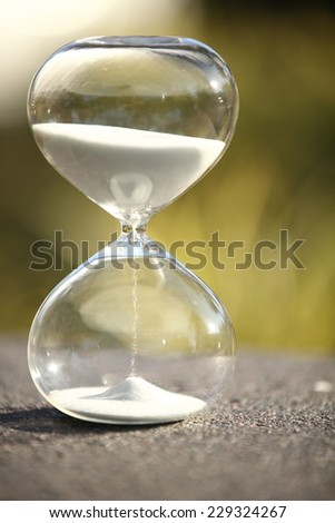 Modern Hourglass -- sand trickling through the bulbs of a crystal sand glass. every second counts. symbol of time. spring countdown. - stock photo