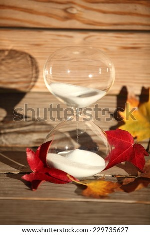 Modern Hourglass -- sand trickling through the bulbs of a crystal sand glass. every second counts. symbol of time. Autumn countdown. - stock photo