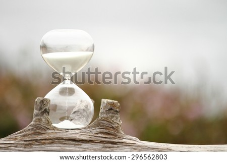 Modern Hourglass -- sand trickling through the bulbs of a crystal sand glass. every second counts. symbol of time. countdown. Time Management. - stock photo