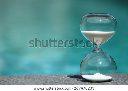 Modern hourglass sits on poolside -- sand trickling through the bulbs of a crystal sand glass. every second counts. symbol of time. summer countdown. - stock photo