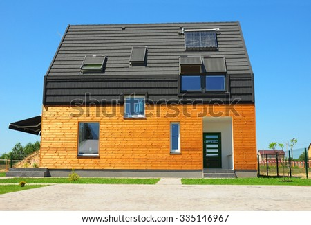 Modern House Exterior Design.  New Building House Energy Efficiency Solution Concept Outdoor. Solar Energy, Solar Water Heater, Solar Panels, Skylights, Ventilation, Installed on Bitumen Tiled Roof.  - stock photo