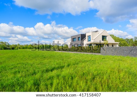 Modern house on green meadow in rural landscape of Krakow, Poland - stock photo