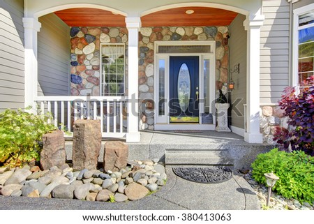 Modern house with navy blue door, and decorative front yard. - stock photo